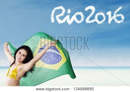 Beautiful girl wearing bikini and holding a Brazilian flag on the beach with text of Rio 2016