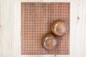 top view two wooden bowls filled black and white stones over empty go game board included clipping path traditional chinese strategy board game sport hobby and recreation poster