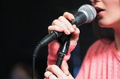 Microphone and unrecognizable female singer close up. Cropped image of female singer in pink dress , singing into a microphone, holding mic with two hands. Copyspace poster