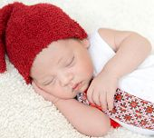 sleeping newborn baby in ukrainian embroidery and red hat with hand on head poster