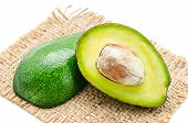 Fresh avocado fruits cit in half on sack background. poster