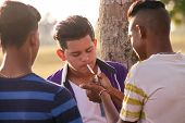 Youth culture young people group of male friends mixed race teen outdoor teenager in park. Hispanic kid smoking cigarette confident boy smoker. Health problems social issues. poster