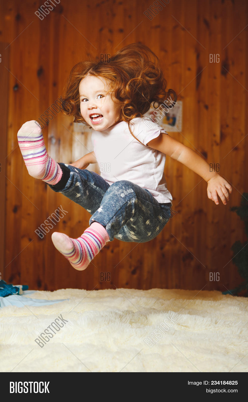 Funny Baby Jumping On The Bed Portrait Of Joyful Girl With Red Hair On The