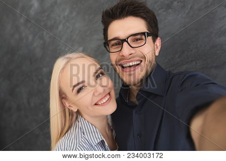 Joyful Young Loving Couple Taking Selfie On Camera, Smiling Together. Capturing Bright Moments, Copy