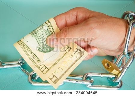 A Hand Chained In A Chain Holds Cash Dollars As A Symbol Of The Buyer And The Consumer Society.