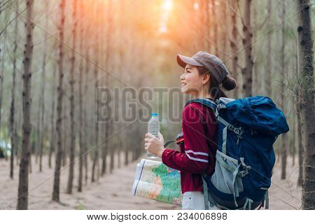 Asia Woman Travel With Backpack,map At Forest Holding Water Go To Destinations, Girl Traveler Doing