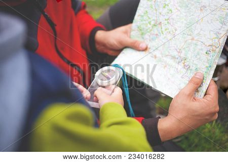 The Boy With His Father Holding A Compass And A Map.