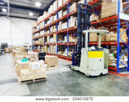 Blurred Photo Of Large Warehouse Logistic Or Distribution Center. Interior Of Warehouse With Rows Of