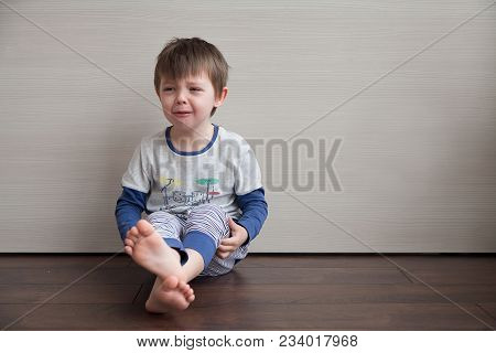 The Boy Is Crying. The Child Is Sitting On The Floor. Frustrated To Tears.