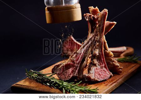 Rack Of Lamb With Rosemary, Spilled With Some Spicies On Wooden Cutting Board Over Dark Background,
