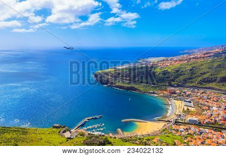 Aerial View Of Machico Bay In Madeira, With An Airplane Taking Off Against The Ocean And The Coastli