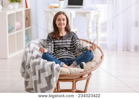 Young woman meditating in lounge chair at home