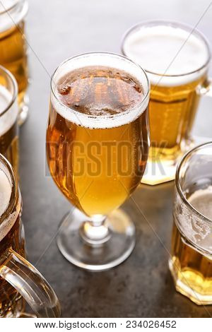Glassware with fresh beer on grey table