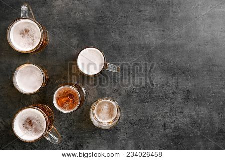 Glassware with fresh beer on grey table, top view