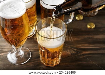 Pouring beer into glass on wooden table