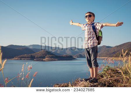 One Happy Little Boy Standing Near A Lake