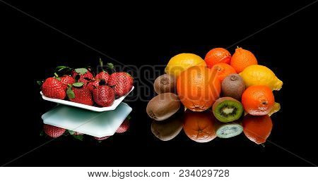 Strawberries And Other Fruits On A Black Background. Horizontal Photo.