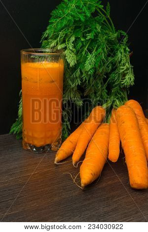 Fresh Carrot Juice And Carrot Bunch Of Carrot On The Black Table