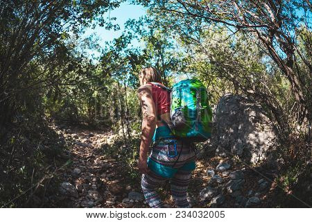 Woman With A Backpack In The Mountains.