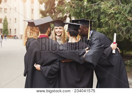 A Group Of Multietnic Students Hugging On Their Graduation. Education, Qualification And Gown Concep