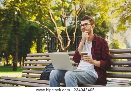Pensive Ypung Man Sitting On Bench, Holding Coffee Cup And Talking On Smartphone, Working On Laptop
