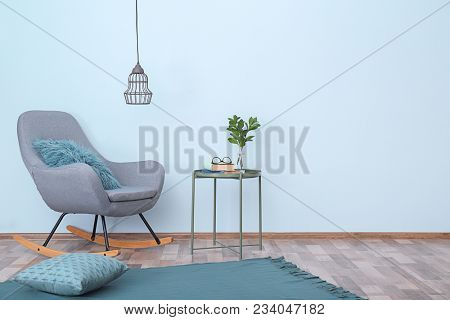 Elegant room interior with comfortable rocking chair near light wall