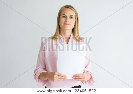 Serious Confident Businesswoman Analyzing Report And Looking At Camera. Calm Attractive Business Exp