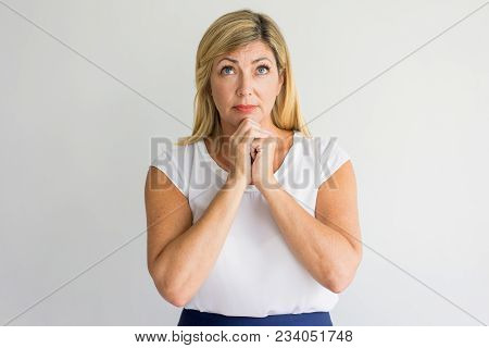Serious Religious Woman Praying For Strength And Looking Up. Calm Lady Holding Hands Together While