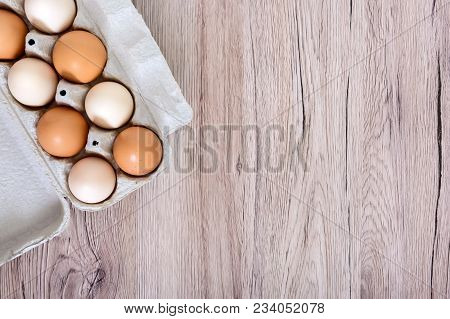 Fresh Raw Chicken Eggs In Carton Egg Box On Wooden Background. The Top View On Brown And White Eggs.