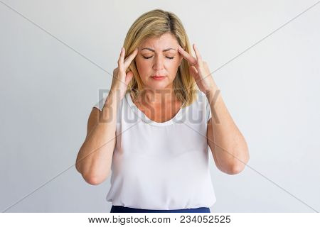 Stressful Mature Woman Suffering From Headache And Touching Temples. Serious Concentrated Lady Feeli