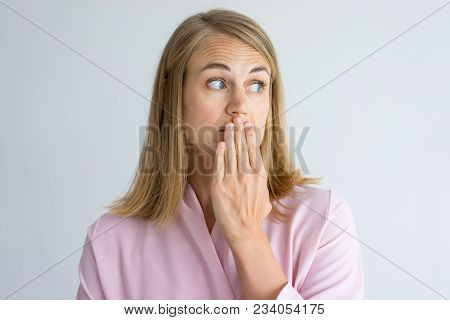 Portrait Of Shocked Young Caucasian Woman Wearing Pink Blouse Covering Mouth With Hand. Fear, Bad Br