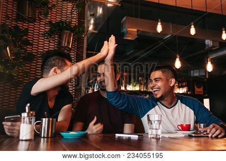 Happy Arabic Young Man Giving High Five To His Friend. Group Of Mixed Race People Having Fun In Loun