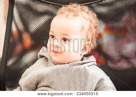 Indoor Portrait Of A Cute Little 1 Year Old Boy Are Sitting On The Chair