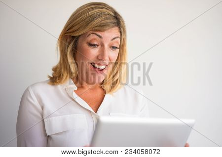 Closeup Portrait Of Surprised Middle-aged Fair-haired Woman Reading News On Tablet Computer. Surpris