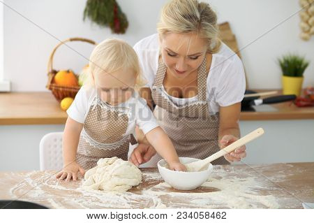 Little Girl And Her Blonde Mom In Red Aprons  Playing And Laughing While Kneading The Dough In The K