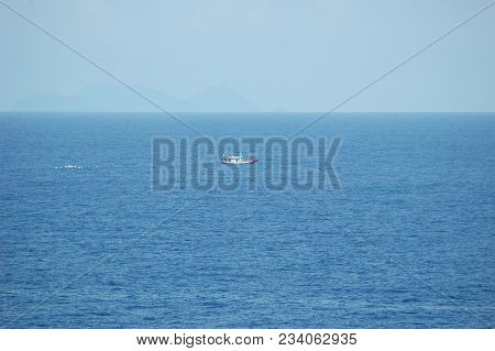 A Small Fishing Boat Is Being Followed By A Flock Of Seagulls. The Boat Looks Small On The Vastness
