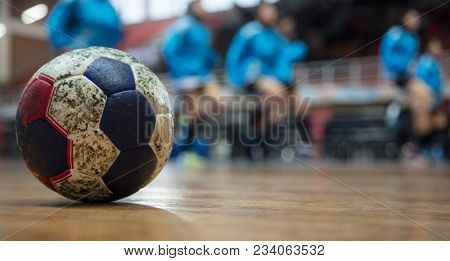 Handball ball on court's floor. Blurred court and exercising team background. Space for text.