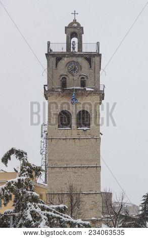 Kozani town, Greece. Snowy belfry of Saint Nikolaos orthodox church. Destination for holidays at Macedonia. Misty sky background.