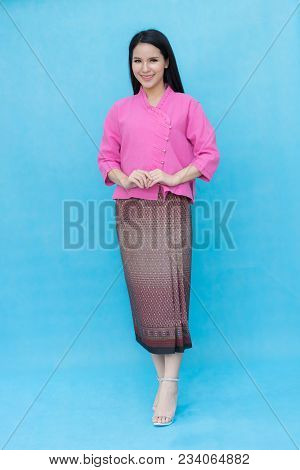 Portrait Beautiful Asian Girl In Traditional Thai Dress Isolated On Blue Sky Background.  Cotton Dre