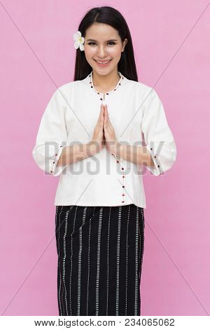 Portrait Of Asian Young Girl In Traditional Thai Dress Praying Isolated On Pink Background. Wai Sawa