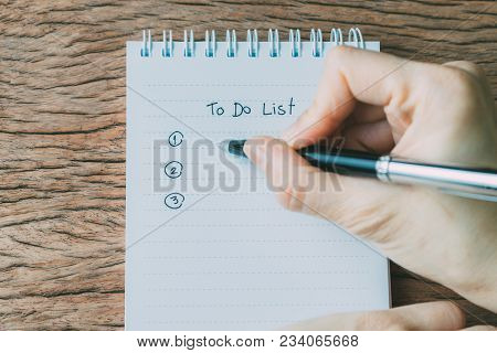 Hand Holding Black Pen Writing To Do List Tasks Prioritized By Number On White Paper Notepad On Wood