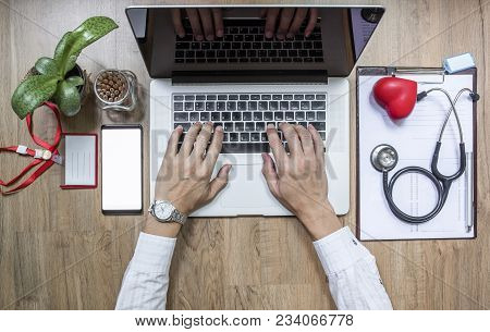 Doctor Working At Office Desk And Using A Laptop Computer, Top View