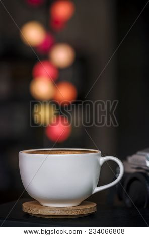Close Up White Coffee Cup On Wooden Plate And Colorful Blur Light Bokeh In Dark Background