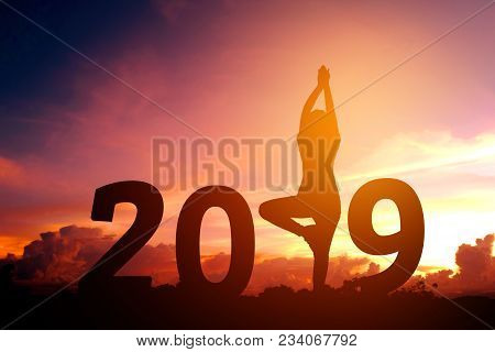 Silhouette Young Woman Practicing Yoga On 2019 New Year