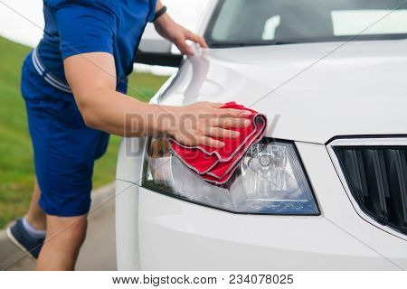 Man Wipes The Car From Dust And Water