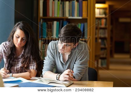 Students writing an essay in a library
