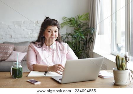 Cute Body Positive Young Chubby Female Freelancer Sitting In Modern Room Interior In Front Of Open L