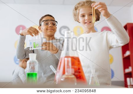 Pleased With Result. Upbeat Teenage Girl And Her Male Classmate Looking At The Test Tube With The Su