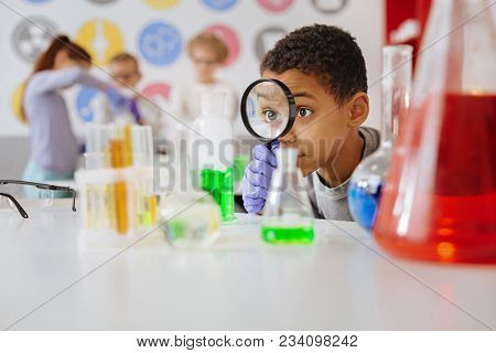 Helpful Tool. Upbeat Teenage Boy Looking At A Chemical Flask Through A Magnifying Glass While Examin