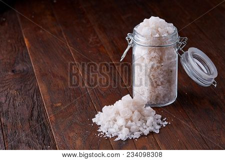 Spa Concept. Bath Salt Pouring Out Of Glass Jar On Wooden Table, Close-up, Selective Focus. Skin And
